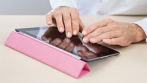 Hände bedienen ein Tablet -